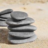 Piles de pierres sur le sable d'une plage Photos libres de droits