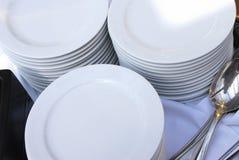 Piles de plaques de restauration avec des cuillères Photo stock