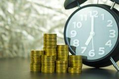 Piles de réveil et de pièces de monnaie sur la table de fonctionnement, heure pour le concept d'argent de l'épargne, opérations b photo libre de droits