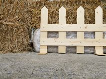 Piles de vieille paille derrière une barrière en bois photographie stock libre de droits