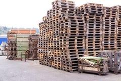 Piles de vieilles palettes en bois dans une cour Photographie stock libre de droits