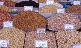 Piles des écrous et des épices colorés à un marché de nourriture image stock