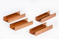 Piles des agrafes de cuivre sur le blanc Photographie stock