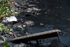 Piles des déchets différents sur l'eau foncée Photographie stock libre de droits