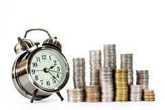 Piles des pièces de monnaie et de l'horloge Photos stock