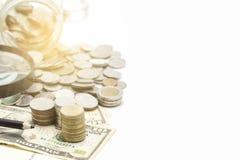 piles des pièces de monnaie et du billet de banque du dollar sur le fond blanc Image libre de droits