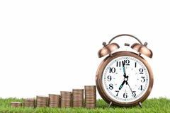 Piles des pièces de monnaie et du réveil sur l'herbe un fond image libre de droits
