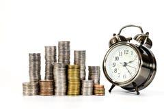 Piles des pièces de monnaie et de l'horloge Photos libres de droits