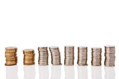 piles des pièces de monnaie sur le fond blanc Photo libre de droits