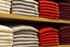 Piles des vêtements multicolores sur les étagères dans le magasin image stock