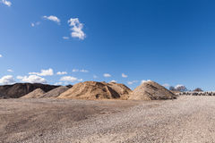 Piles du gravier au chantier de construction sous le ciel bleu lumineux Photos stock