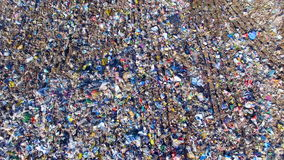 Piles of empty bottles, bags and other plastic in the garbage dump. Aerial.
