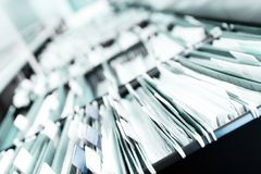Piles of files. Multiple rows of filing cabinets in an office or medical establishment, overflowing with files.  Narrow depth of field to emphasize the Royalty Free Stock Images