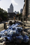 Piles of garbage in New York City. Piles of garbage in blue plastic bags waiting for collection from side street in New York City Royalty Free Stock Images