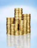 Piles of gold coins. Different height piles of gold coins on blue background Stock Photos