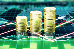 Piles of gold coins on the screen with business chart Stock Photography
