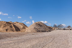 Piles of Gravel at Construction Site under Bright Blue Sky Stock Images