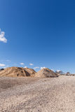 Piles of Gravel at Construction Site under Bright Blue Sky Stock Image