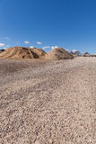 Piles of Gravel at Construction Site under Bright Blue Sky Stock Photos