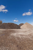 Piles of Gravel at Construction Site under Bright Blue Sky royalty free stock images