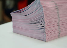 Piles of handout papers placed on table Stock Photo
