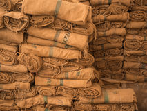 Piles of hemp sacks. Background created by piles of hemp sacks stored in rolls and some with identifying numbers Stock Photography
