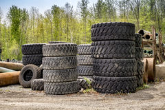 Piles of machinery tires. Large industrial heavy machinery used tires piled up in construction company yard Stock Photo