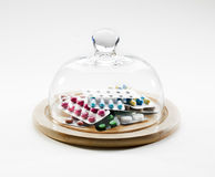 Piles of medication tablets under globe Stock Photo