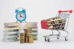 Piles of money, an alarm clock is on them, a trolley with coins royalty free stock images