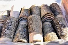 Piles of old roof tiles in many rows with different number in any column. The ancient tiles are stained with dust and lichens to stock photo