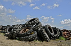 Piles of old tractor tires. A recycling center contains piles of huge and old tractor tires royalty free stock photo