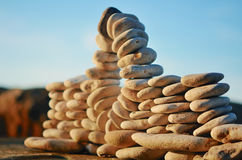 Piles of pebbles. Stone arch between the pebbles on the coast Royalty Free Stock Images