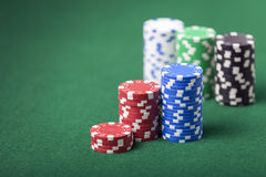 Piles of poker chips. Several piles of poker chips on a green gambling table Royalty Free Stock Images