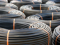 Piles of PVC Piping. Tightly coiled PVC irrigation tubing royalty free stock images