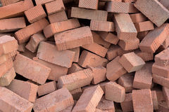 Piles of Red Construction Bricks. Scattered on the ground. Copyspace area for construction or building industry designs and text overlays Stock Images