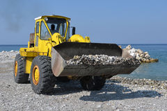 Piles of shingle dumped on the beach shore replenish and widen. Large trucks restore sand on the coast expanding the beach Stock Image