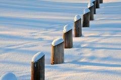 Piles in snow field stock photo