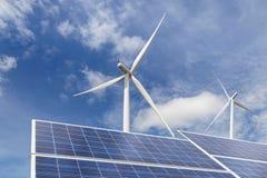 Piles solaires avec des turbines de vent dans la station hybride de systèmes de centrale sur le fond de ciel bleu Images stock