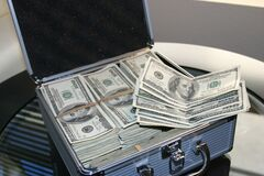 Piles of U.s. Dollar Bills on Silver and White Suitcase Royalty Free Stock Photo