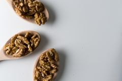 Piles of walnuts in wooden spoones on white background. Nuts for health. Selective focus. Piles of walnuts in wooden spoones on white background. Nuts for stock photos