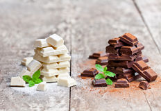 Piles of white and dark chocolate slices  with mint on an old woo Stock Images