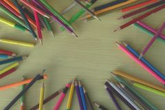 Piles of wood pencils on the floor, yellow desk in the art classroom. Art room signboard stock images