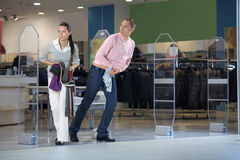 Pilferers in shop. The pair steals clothes from shop and escapes stock image