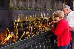 Pilger, die votive Kerzen als Erfüllung von Versprechen brennen Stockfotografie