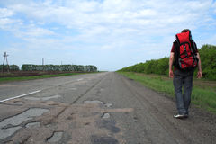 Pilgrim. Man with a backpack on a back goes on edge of road Royalty Free Stock Photo