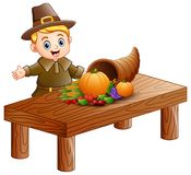 Pilgrim boy with cornucopia of fruits and vegetables on wooden table. Illustration of Pilgrim boy with cornucopia of fruits and vegetables on wooden table Stock Photo