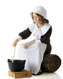 Pilgrim Girl Stirring. An elemantary-aged Pilgrim girl sitting on an old log while stirring food in a cauldron for the first Thanksgiving feast.  One a white Royalty Free Stock Image