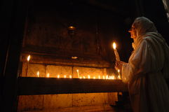 Pilgrim in Jerusalem. September 16, 2006 - A pilgrim prays by candlelight against the wall of Christ's tomb in the Church of the Holy Sepulcher, Jerusalem Stock Image