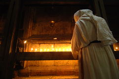 Pilgrim Praying in Jerusalem. September 16, 2006 - A pilgrim prays by candlelight against the wall of Christ's tomb in the Church of the Holy Sepulcher Royalty Free Stock Photos