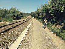 Pilgrim walking along a railway track, Galicia, Spain Stock Photos